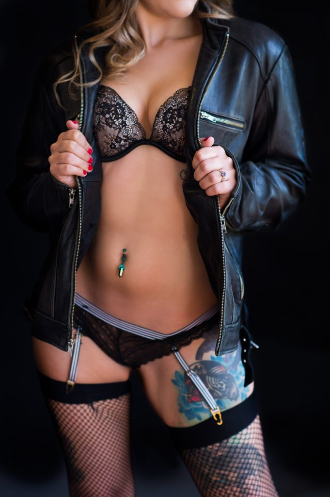 Woman gripping leather coat with black lace bra, and lace panties, and garter.