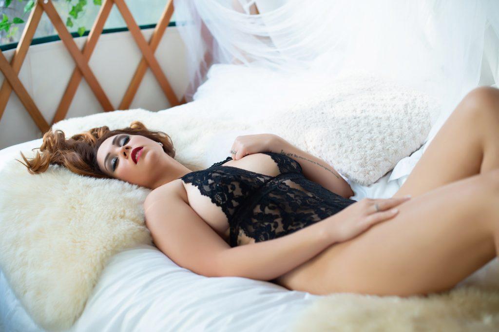 Treehouse Boudoir - Woman lying on her back grabbing her black lace bodysuit near her left breast.