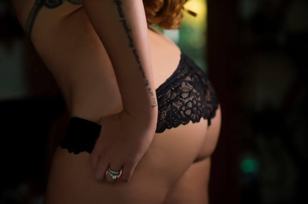 Woman tugging at her black lace panties with her butt 45 degrees to the camera