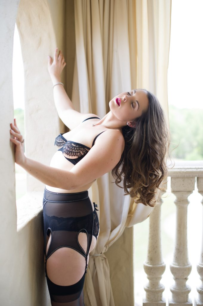 Woman Arching Back away from the balcony edge wearing black lace bra and black garter belt