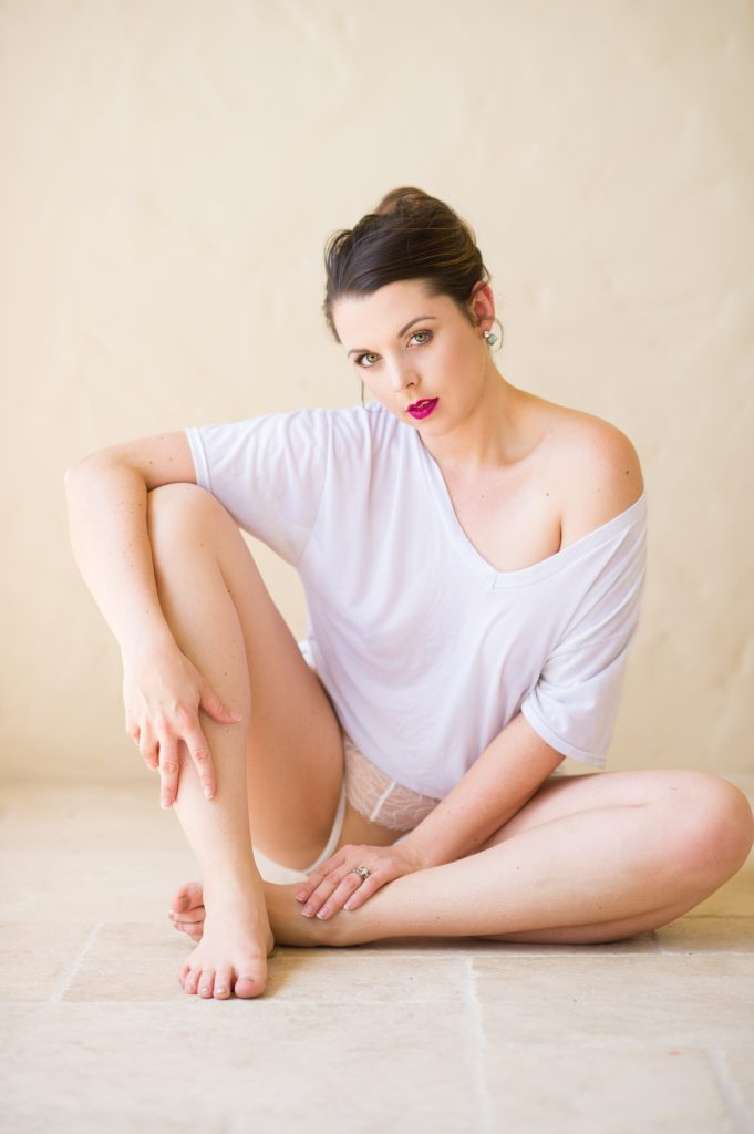 woman with her hair pinned up sitting up facing the camera while wearing a white tshirt and white lace panties