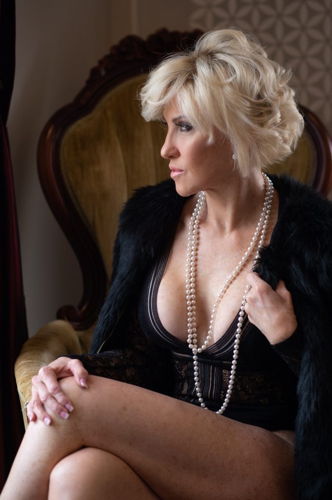 Woman Sitting in chair wearing fur coat and pearls and black body suit gazing out the window